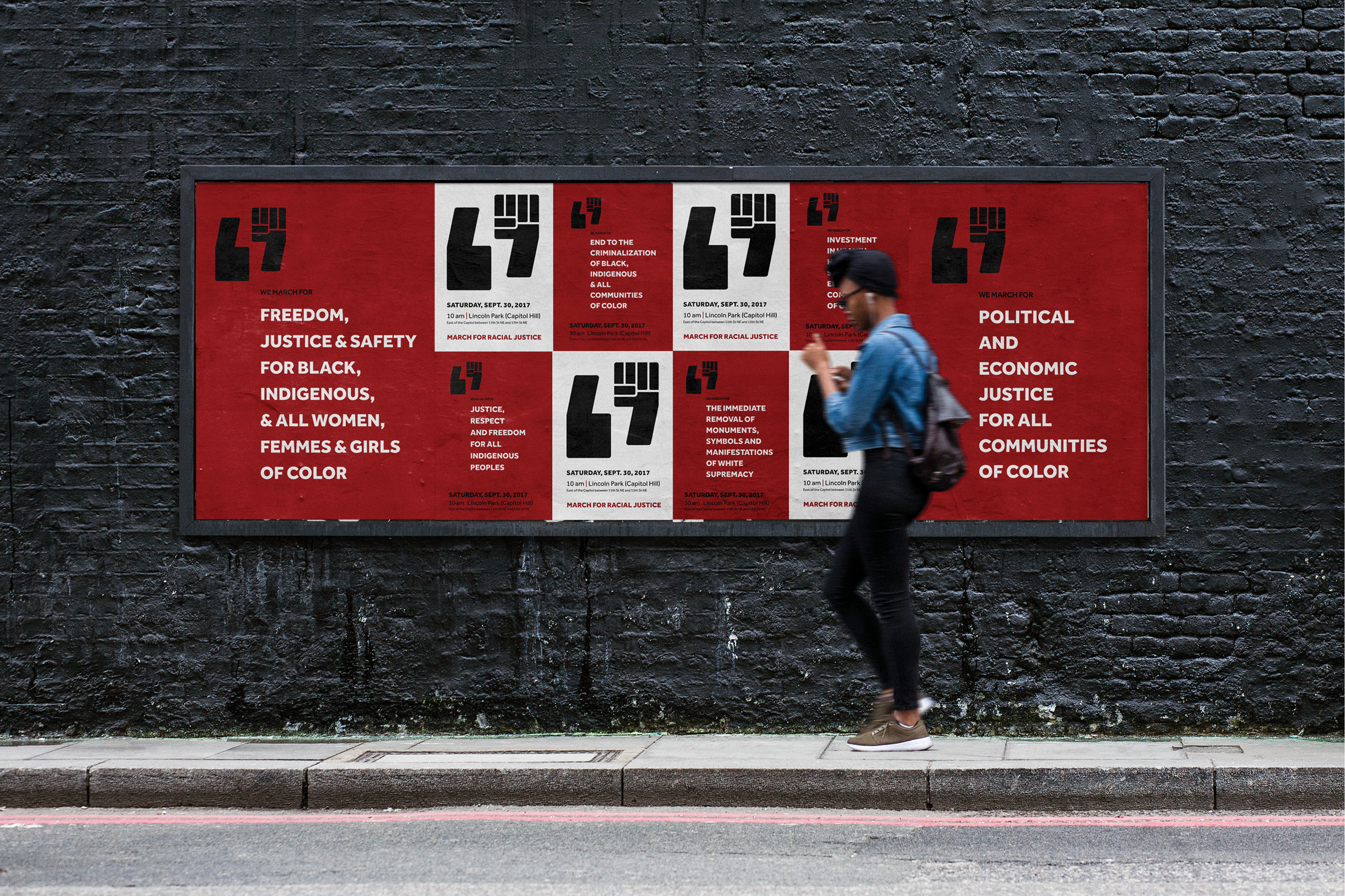 A woman walking in front of a series of promotional wheat-pasted posters for the March for Racial Justice. The posters alternate red and and white, announcing the date and time and the founding principles of the organizers.